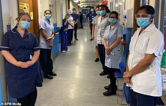 All clear: Staff line a corridor at the hospital to say goodbye to Mr and Mrs England who continue to recover from the virus at home in Leicester